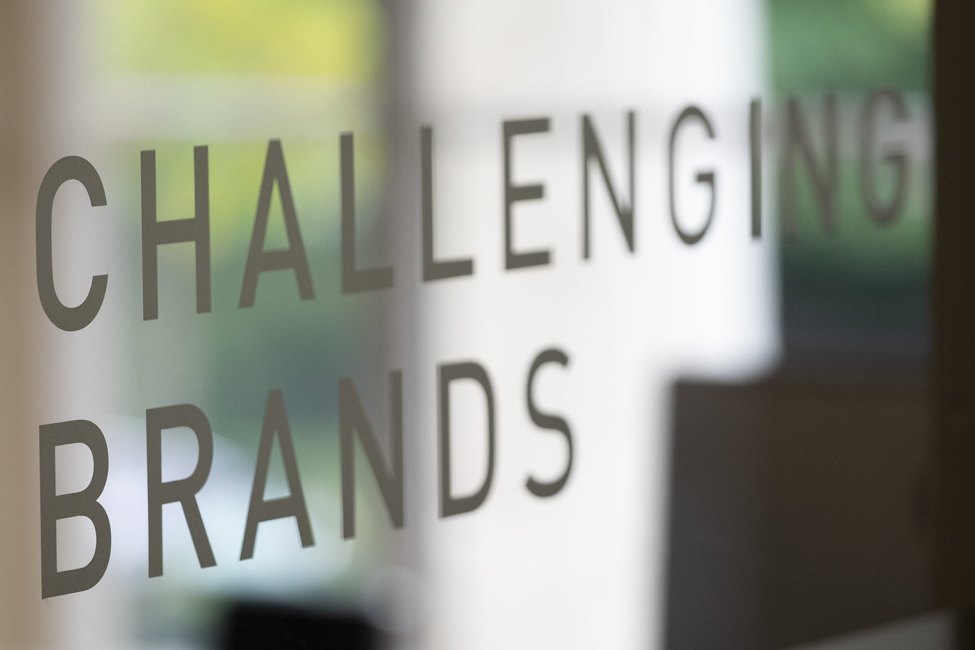 A sign saying challenging brands etched onto a window in an office window at chalk and ward