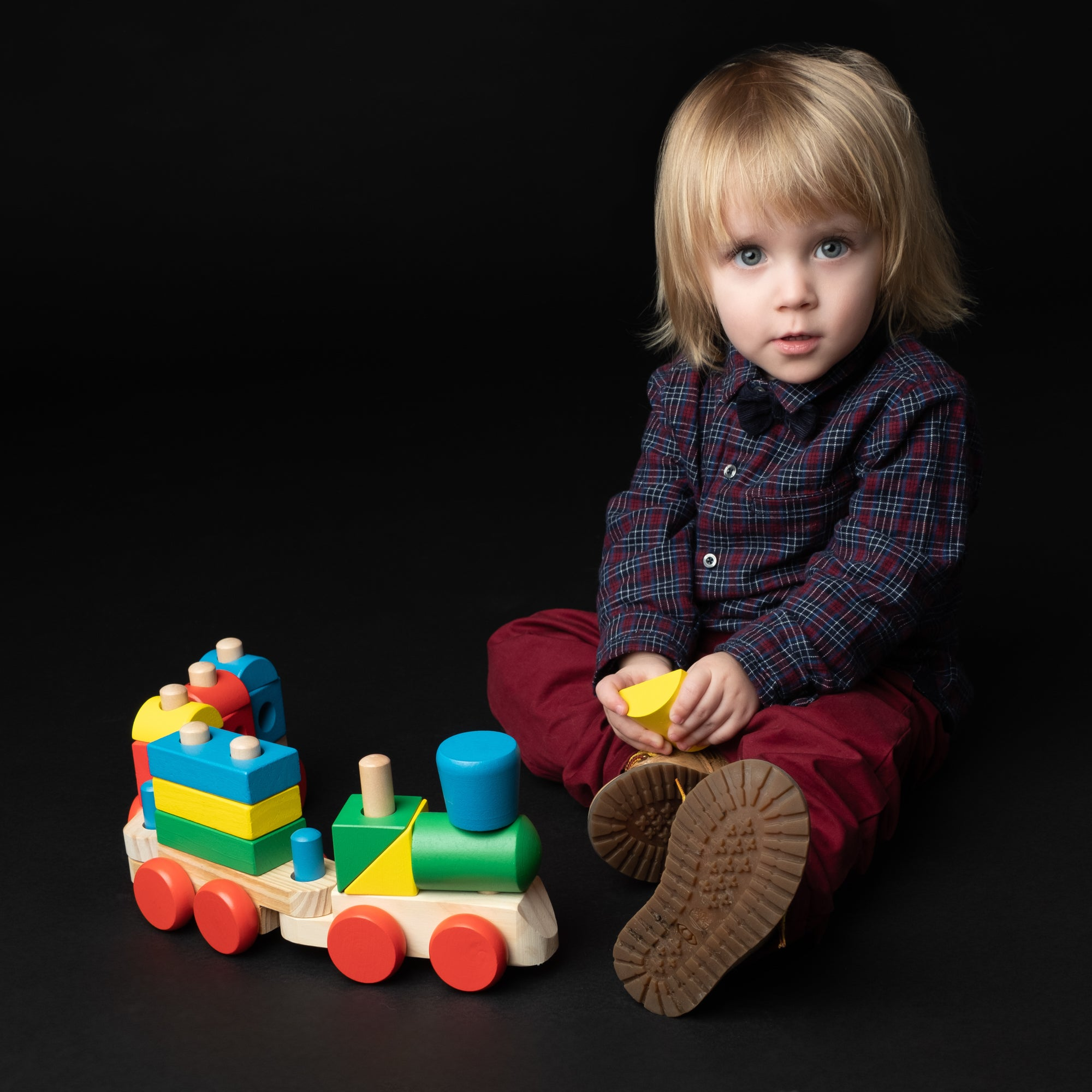 Cute_blonde_haired_Blue_eyed_toddler_in_red_trousers_plays_with_wooden_train_on_the_floor.jpg