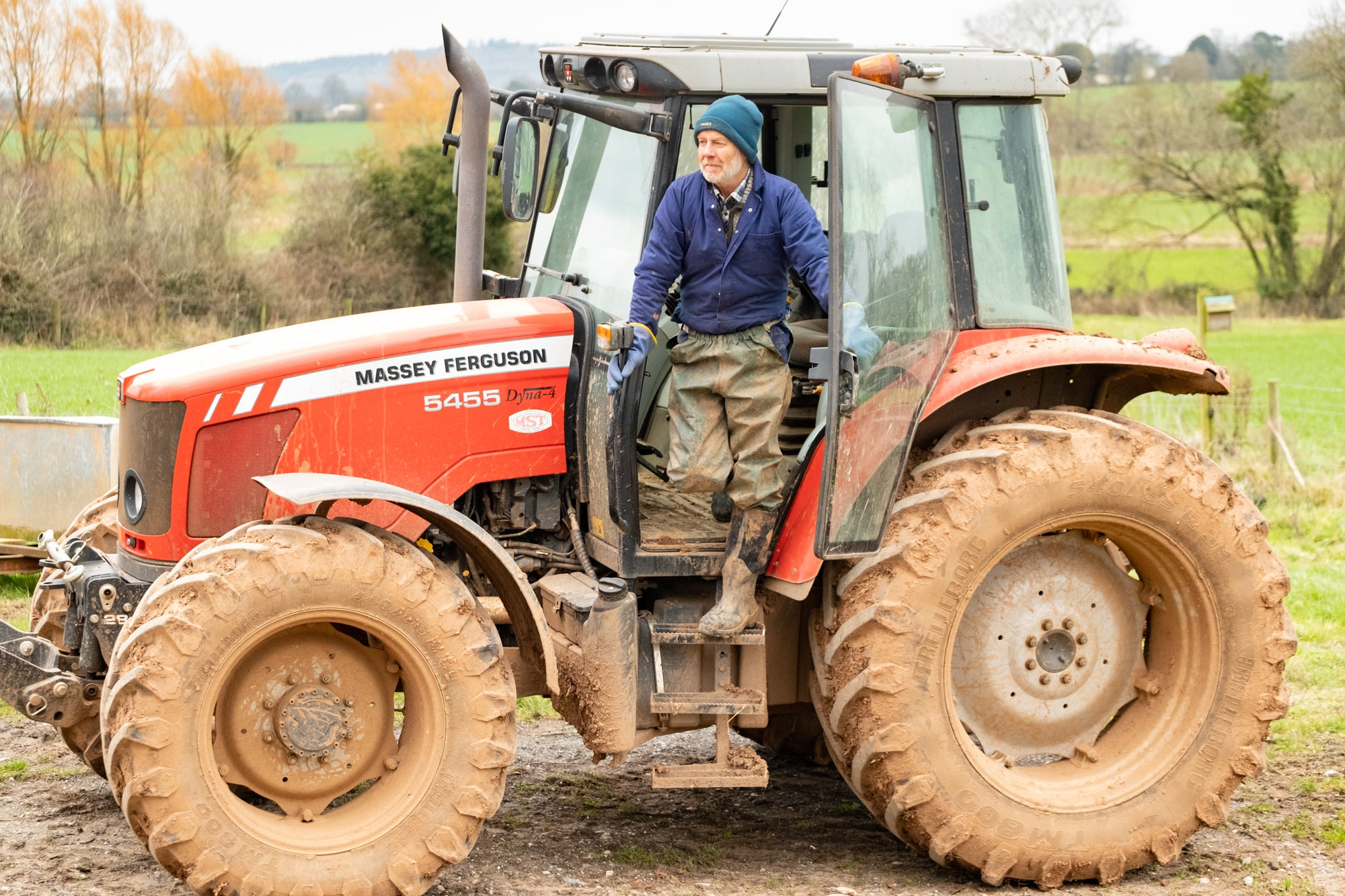 Henry_Gent_in_Woolly_hat_and_waterproof_trousers_coming_down_steps_of_his_tractor.jpg