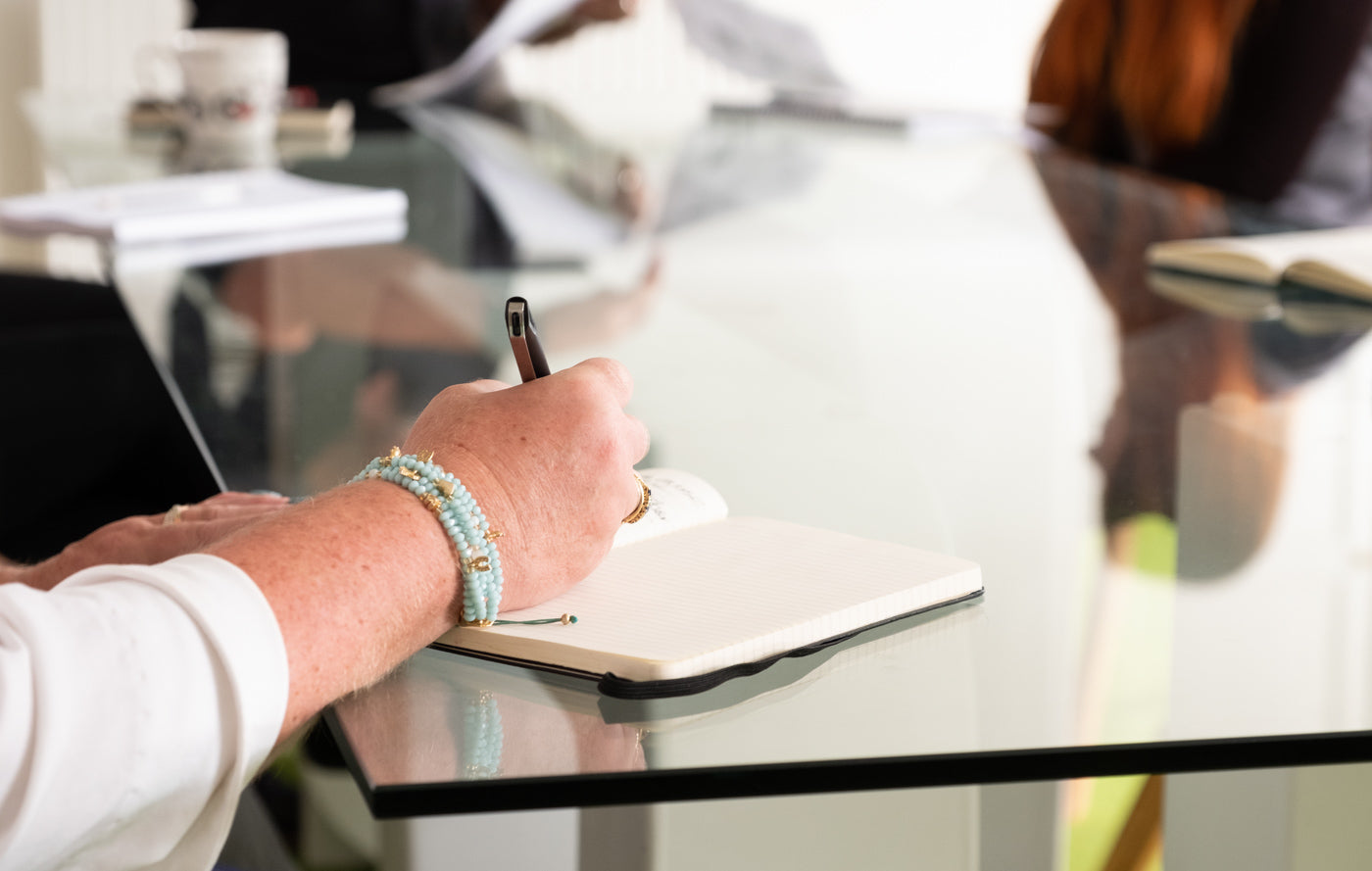 Ladies_bangled_hand_writing_in_notepad_on_glass_boardroom_table.jpg