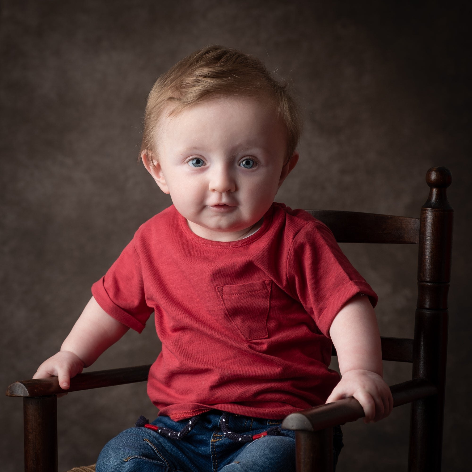 Redheaded_toddler_in_red_T-shirt_and_jeans_sat_in_miniature_armchair.jpg