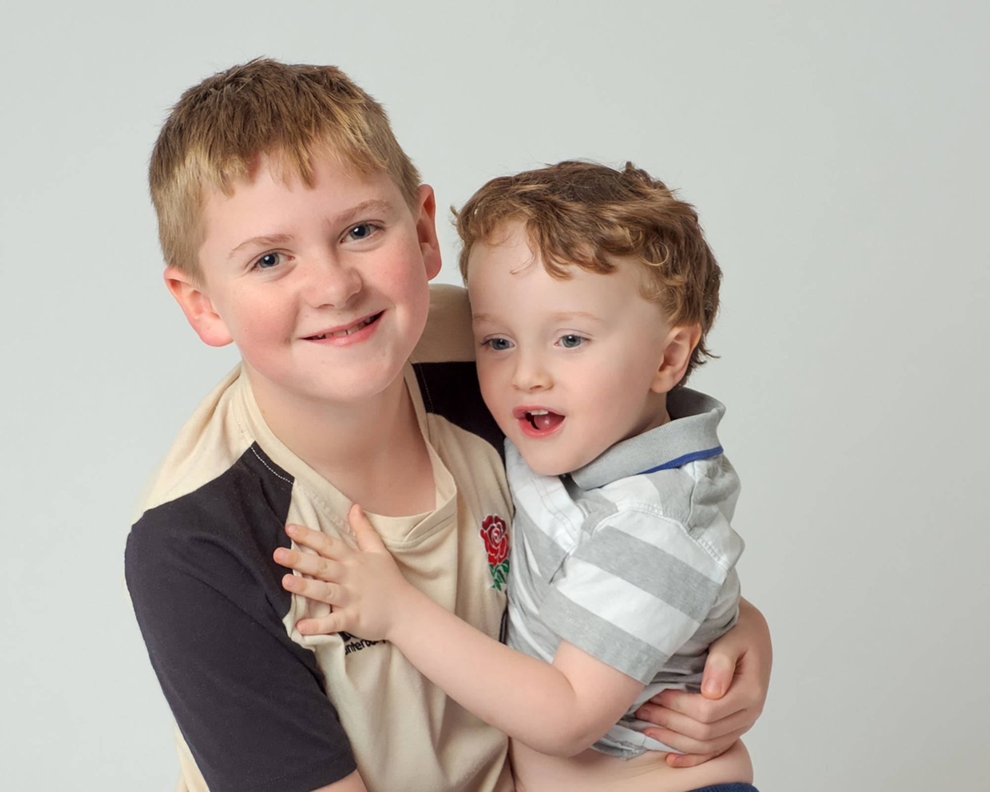 Young_boy_being_cuddled_by_older_brother_on_white_background_smiling.jpg
