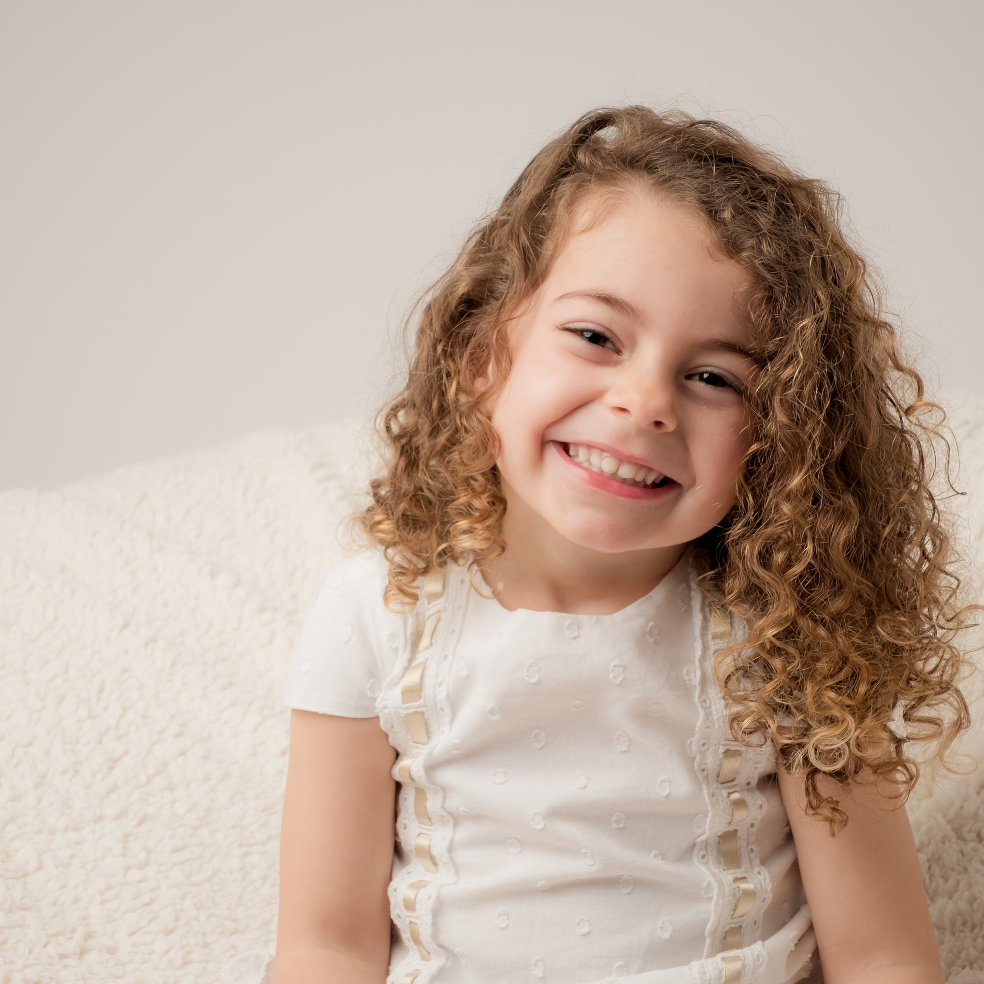 Young_girl_with_long_brown_curly_hair_wearing_a_white_dress_has_a_big_grin_on_her_face.jpg