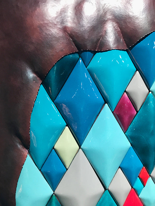 detail of sculptural copper wall art with colored diamond pattern