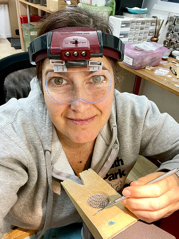 Catherine Grisez wearing optivisor at the work bench carving little wax flowers to be cast in silver and gold