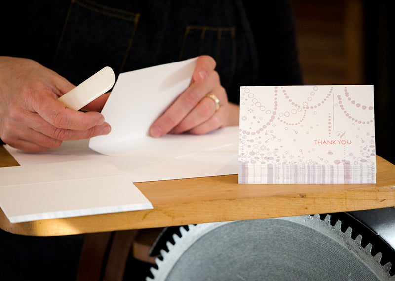 folding cards by hand at Orange House Letterpress, custom Thank You card for CG Jewelry