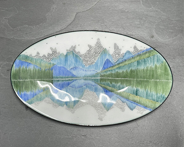 Reflect, and copper and glass enamelware oval bowl hand drawn with blue and green and black reflecting patterns by Seattle artist Catherine Grisez