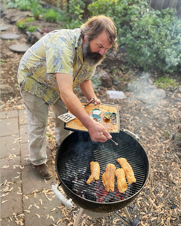 Rob grilling cod with spices on a lump charcoal grill