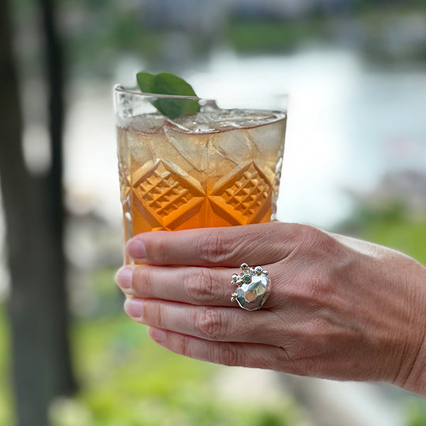 silver, gold, and aqua tourmaline statement ring with gin cocktail at the lake