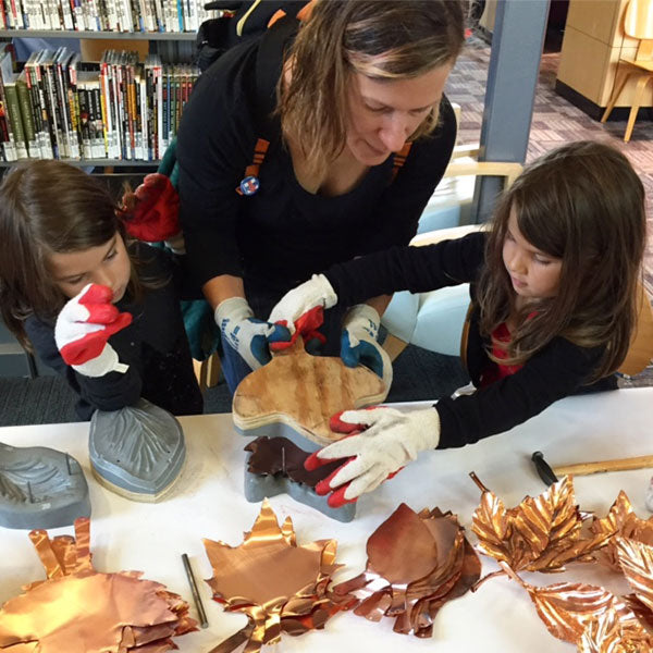mom and kids making copper leaves for Part You collaborative art installation by Seattle artist Catherine Grisez