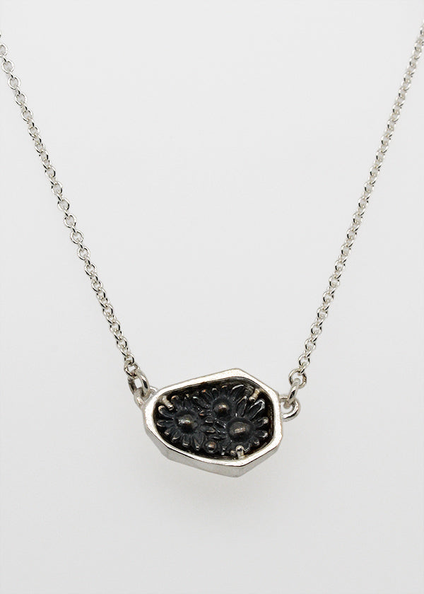 silver rock with darkened flower bloom, a necklace to symbolize strength and inner beauty handmade by artist Catherine Grisez