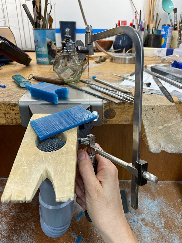 sawing wax block into future tiny flower that will be cast in metal handcrafted jewelry by Catherine Grisez