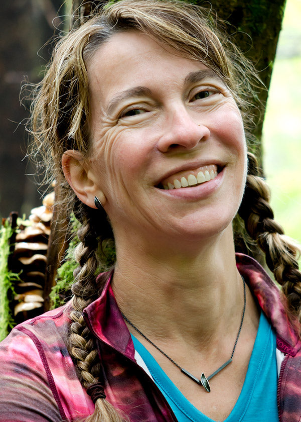 Wendy Woldenberg enjoying a moment in the forest with crazy mushroom tree wearing Catherine Grisez Jewelry