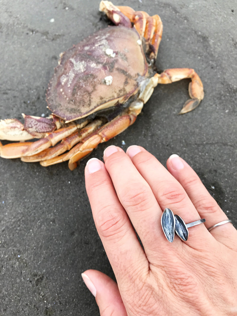 double leaf black silver ring on hand next to colorful crab on beach