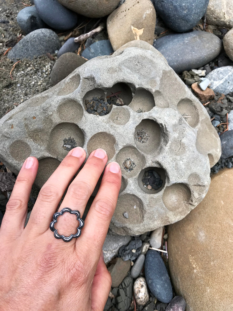 hand wearing dark silver scallop circle ring next to grey rock filled with circles and holes