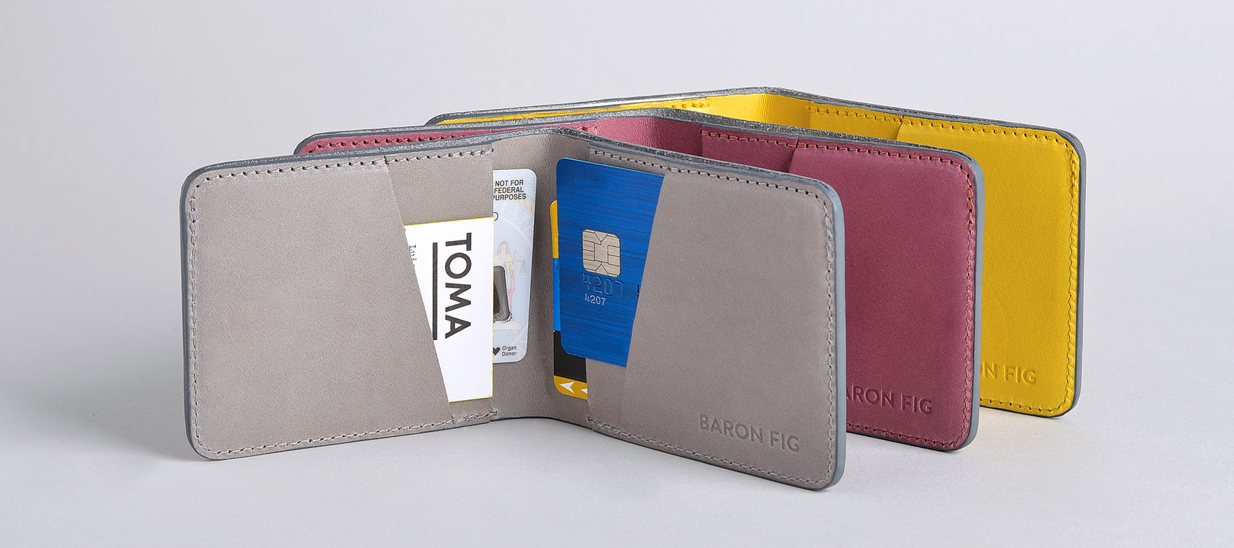 Slim bifold wallets in charcoal, fig wine, and yellowgold