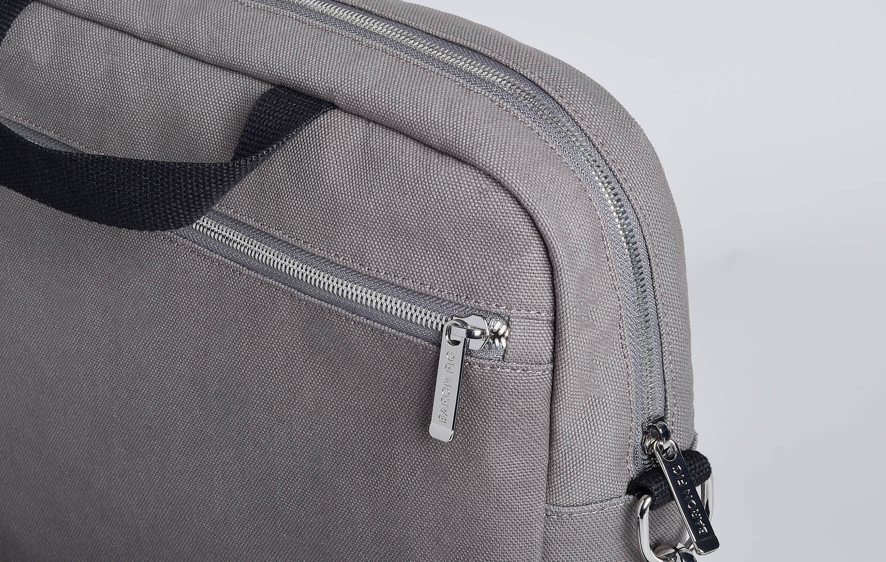 Close up of hardware on charcoal messenger bag