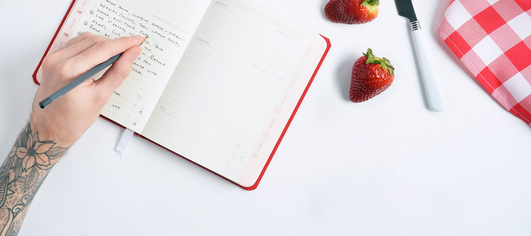 Open savor journal with strawberries, butter knife, tablecloth