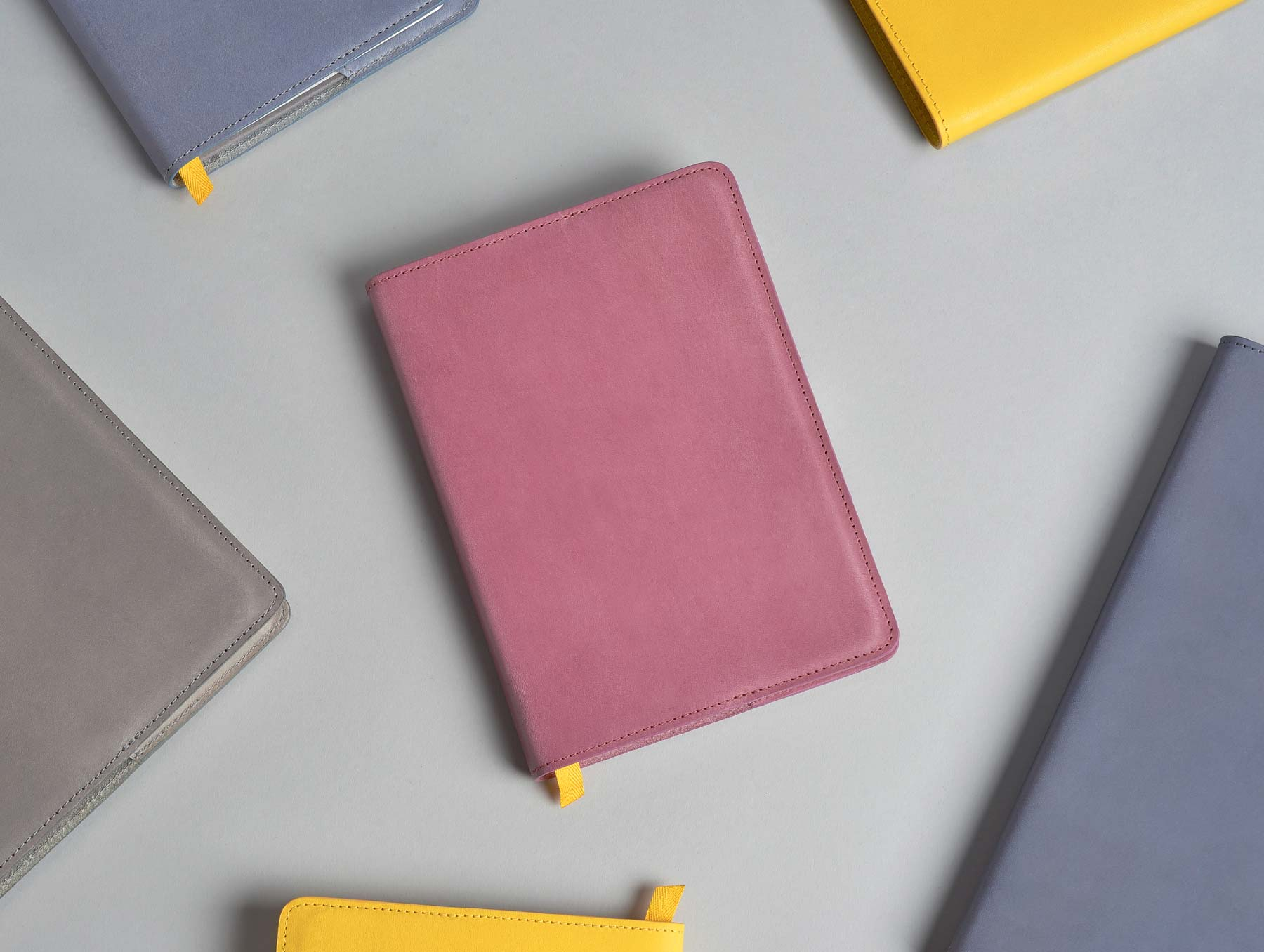 Confidant notebooks in fig wine, charcoal, yellowgold, and blue slate guardians