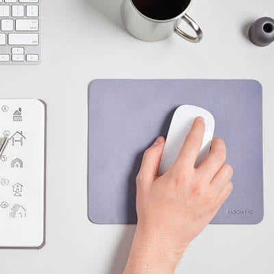 Hand using computer mouse on a blueslate leather mousepad.