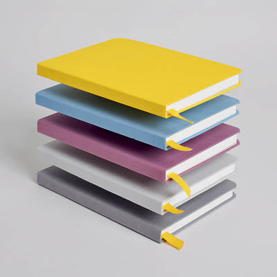Stacked confidant hardcover notebooks in colors yellowgold, blue slate, fig wine, light gray, and charcoal.