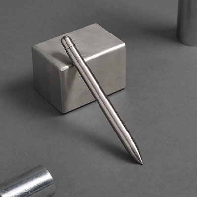 Stainless steel squire rollerball pen decoratively leaning against stainless steel block.