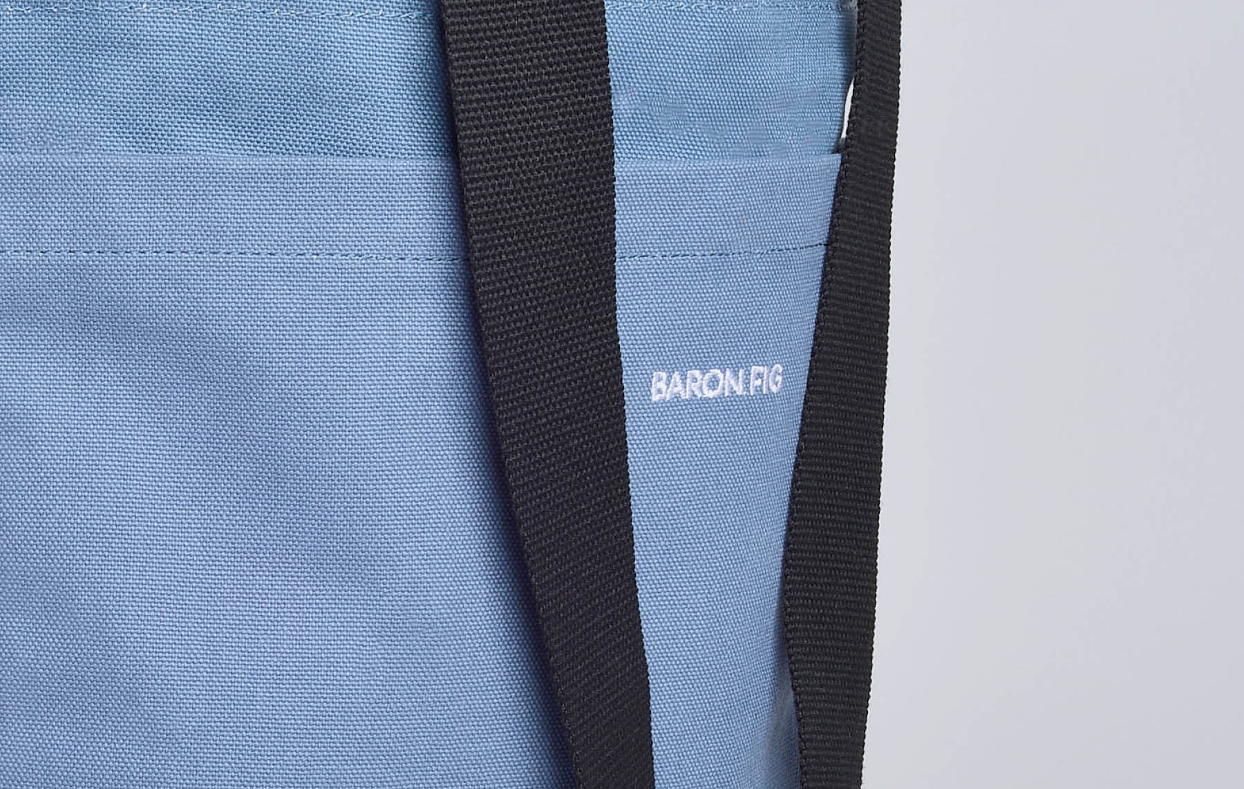 close up of black handles and baron fig logo on blue slate tote