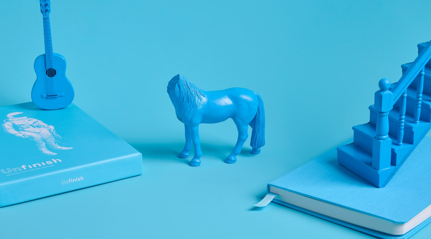 Blue props on blue background with Unfinish notebook