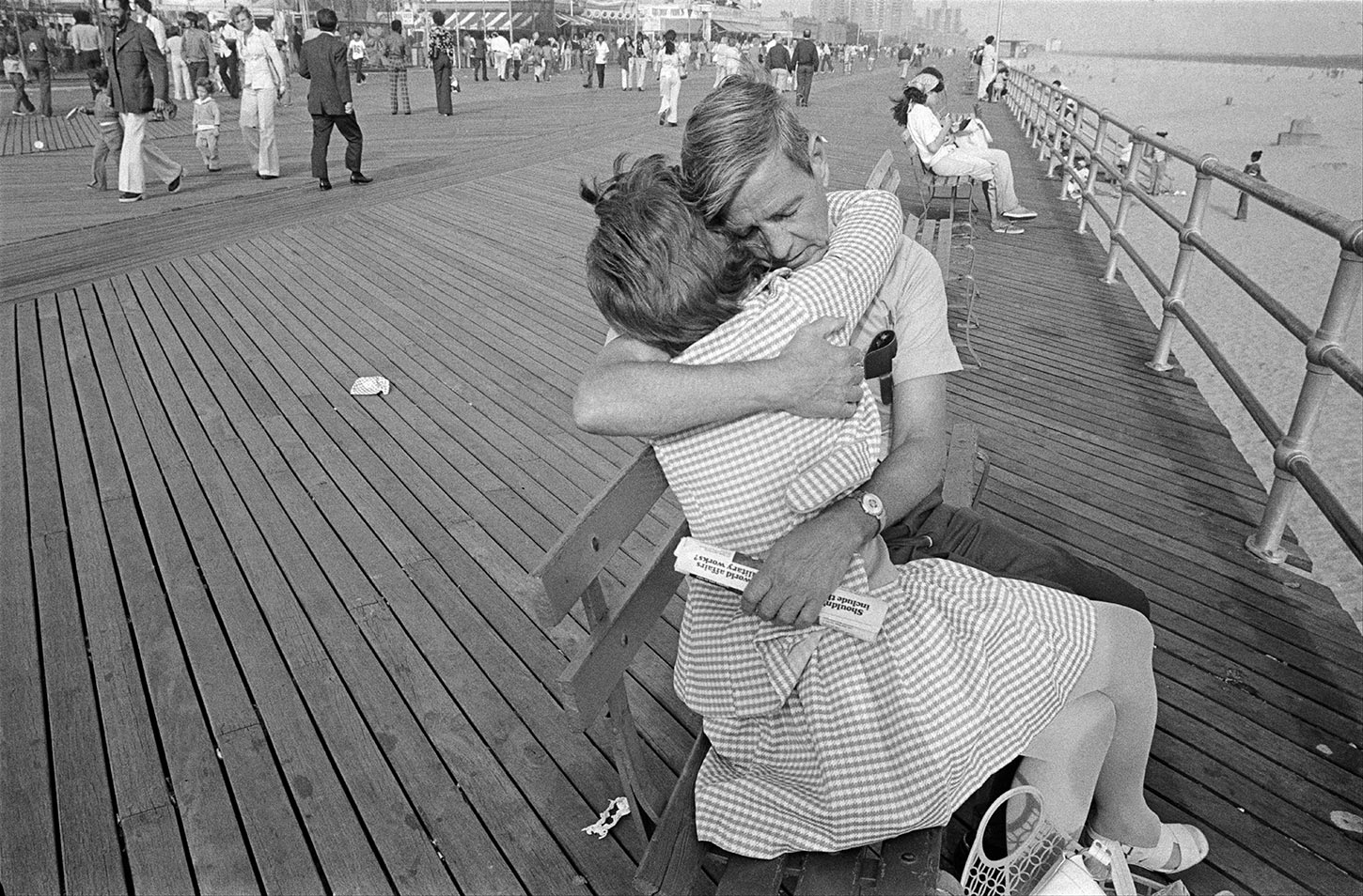 A couple embraces on the boardwalk by the beach. Coney Island, NY. USA. 1977.