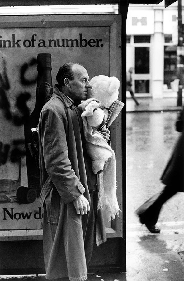 Man with Teddy Bear at bus stop. Cardiff, Wales. 1973.