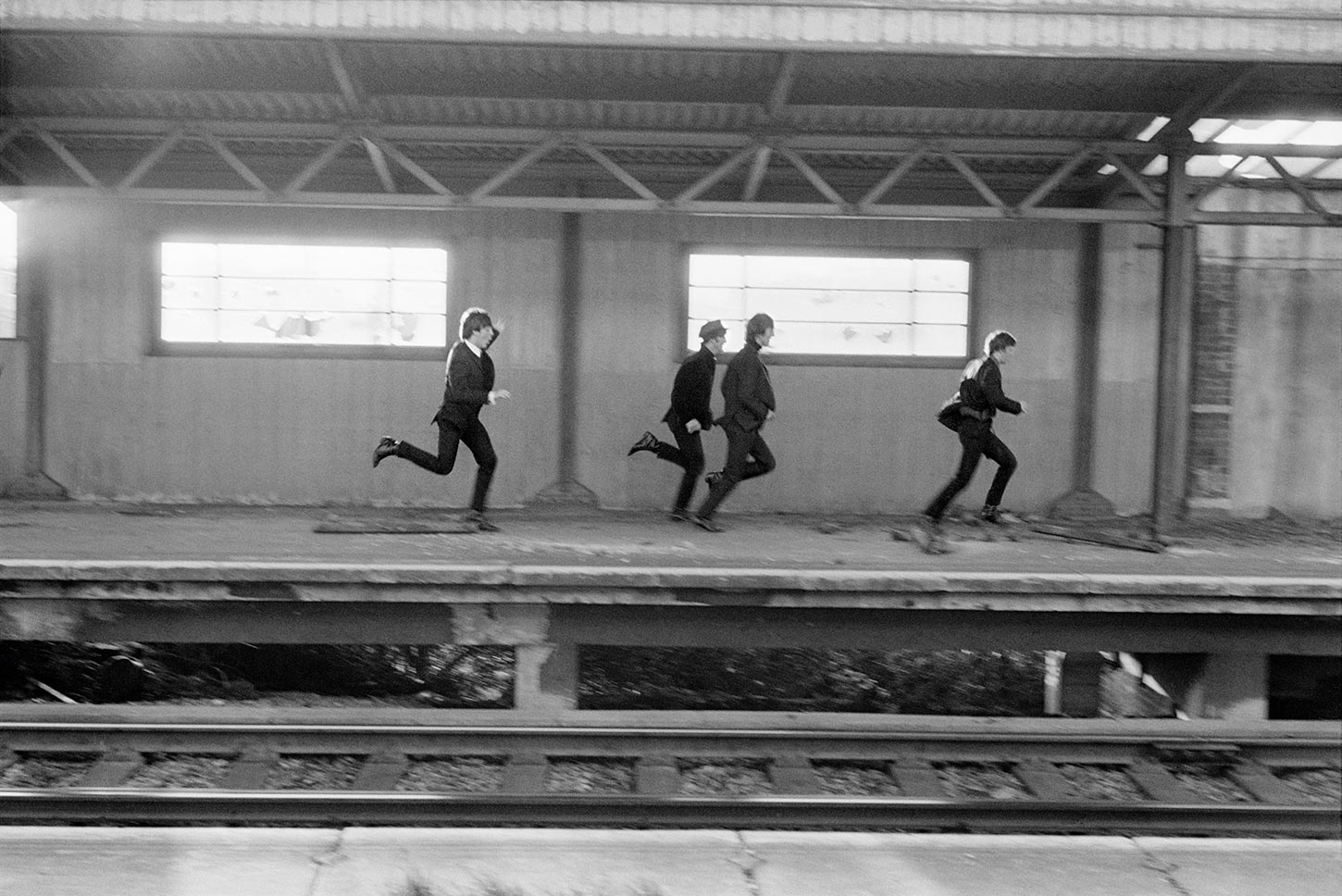 The Beatles running on train platform. London, England. 1964.