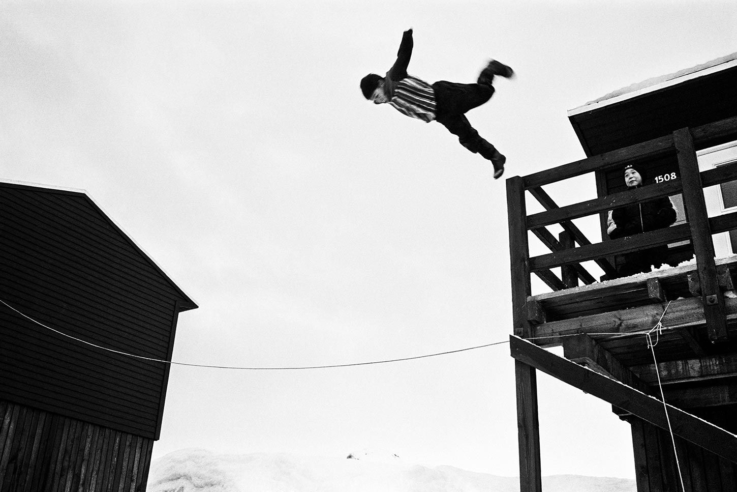 Boy doing somersault. Tiilerilaaq, Greenland. 2001.