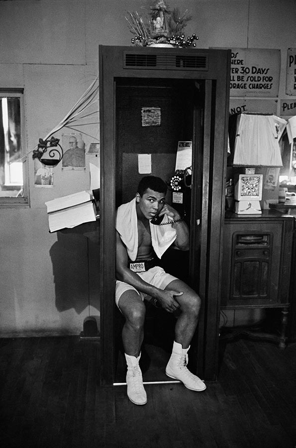 Muhammad Ali takes a break from training to talk on the phone. Chicago, Illinois. 1966.