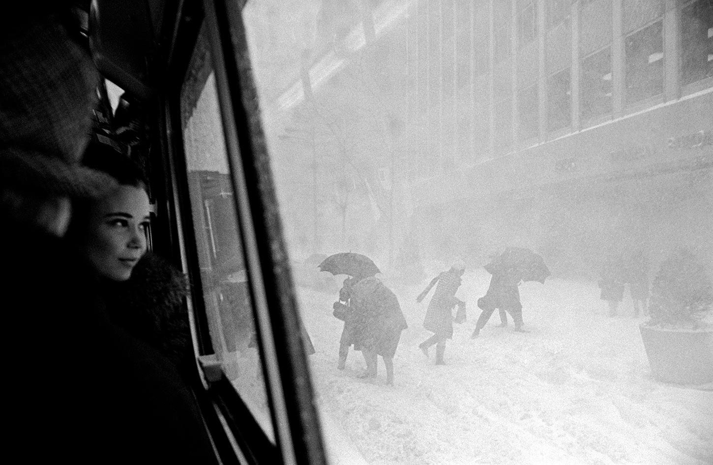 Girl in bus and figures in street during snowstorm. New York City. 1967.