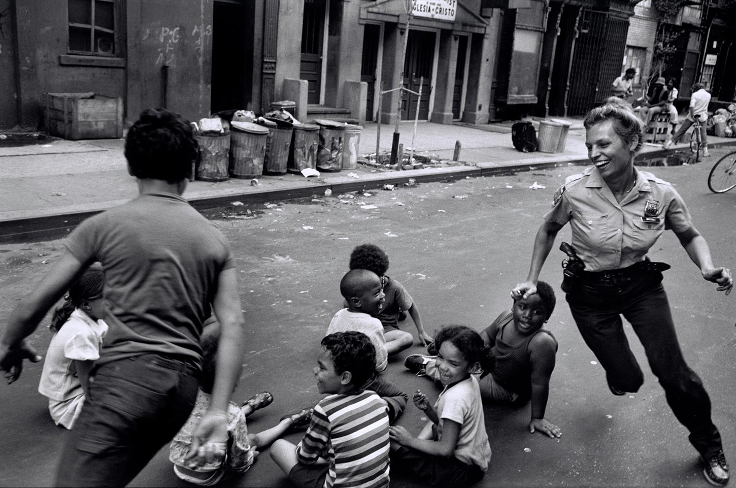 A policewoman plays with local kids in Harlem. New York City, New York. 1978.