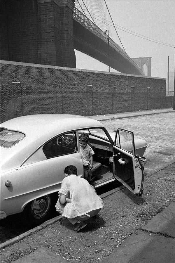 Father and son on streets under the Brooklyn Bridge. New York City, 1955.