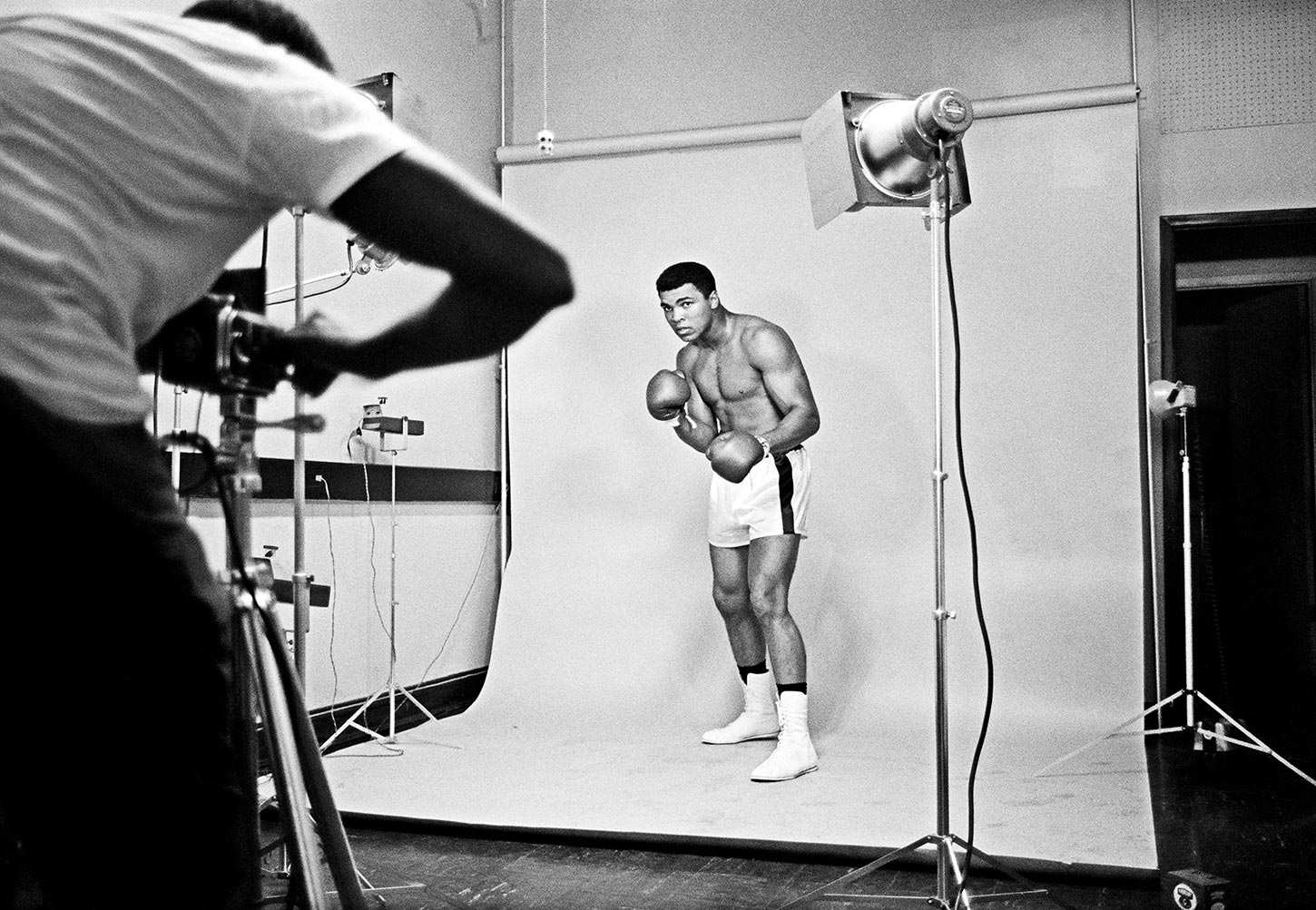 Muhammad Ali in a boxing outfit posing for a studio photographer. Chicago, Illinois. 1966.