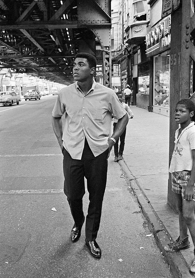 Muhammad Ali walks underneath elevated trains. Chicago, Illinois. 1966.