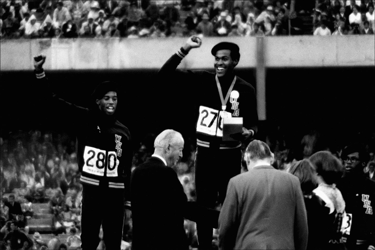 Athletes Larry James, Lee Evans and Ron Freeman clutching their fists on the podium at the 1968 Olympic Games.