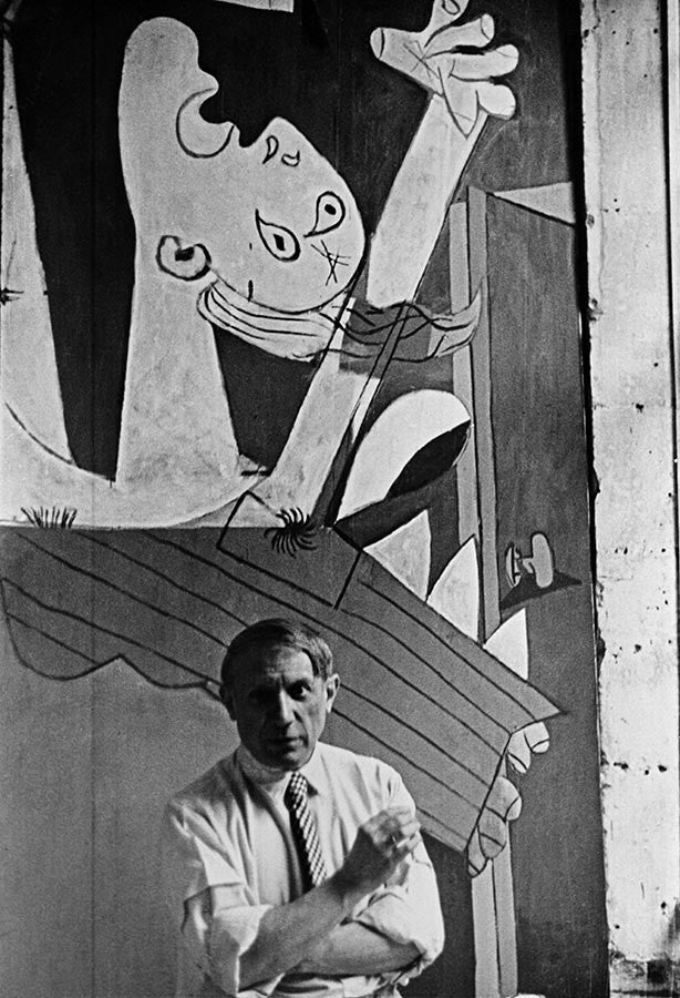 Pablo Picasso in front of his painting, Guernica. 1937.