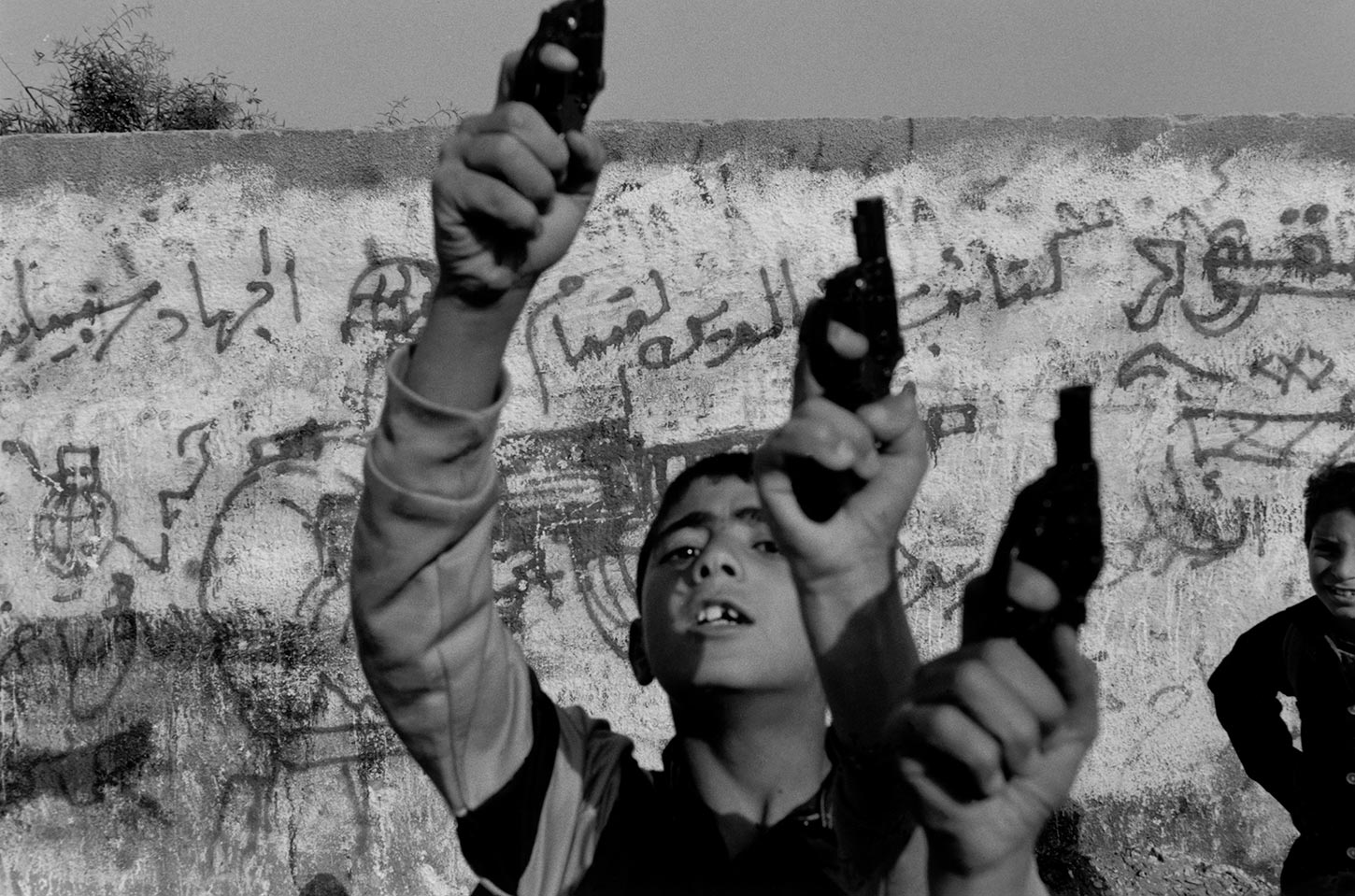 Children holding toy guns in the air. Gaza. 1993.