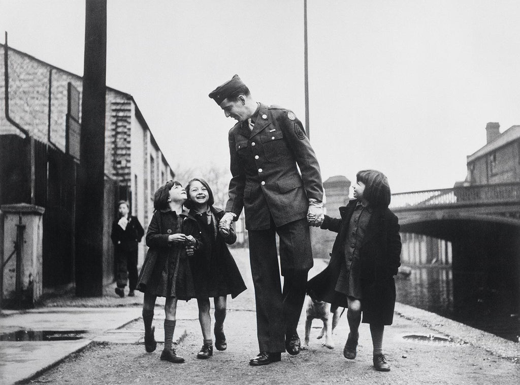 An American soldier with British war orphans adopted by his unit. London, England. January-February 1943.