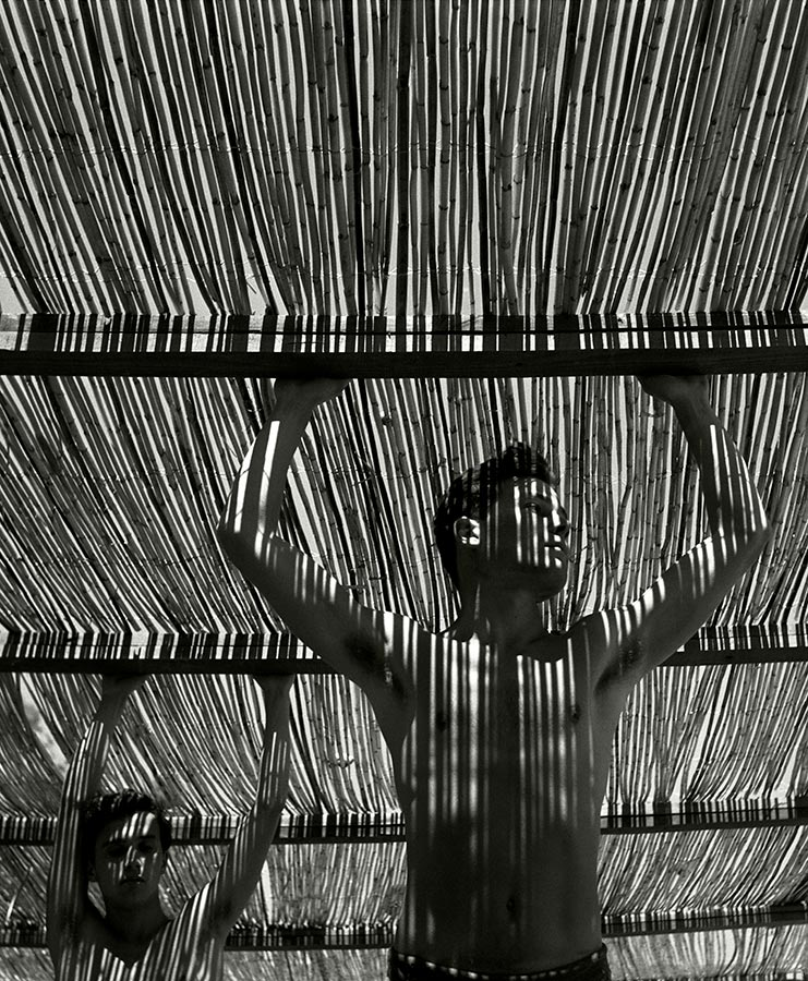 Young men under reed roof. Torremolinos, Andalucia, Spain. 1951.