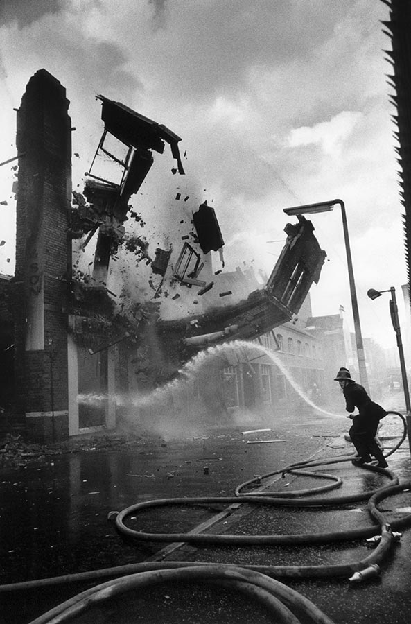 Wall crumbles down after been set on fire. Belfast, Northern Ireland. 1972.
