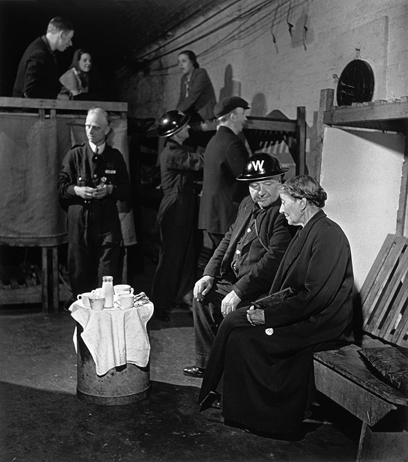 Home Guard warden and woman share tea in an air-raid shelter. England. 1941.