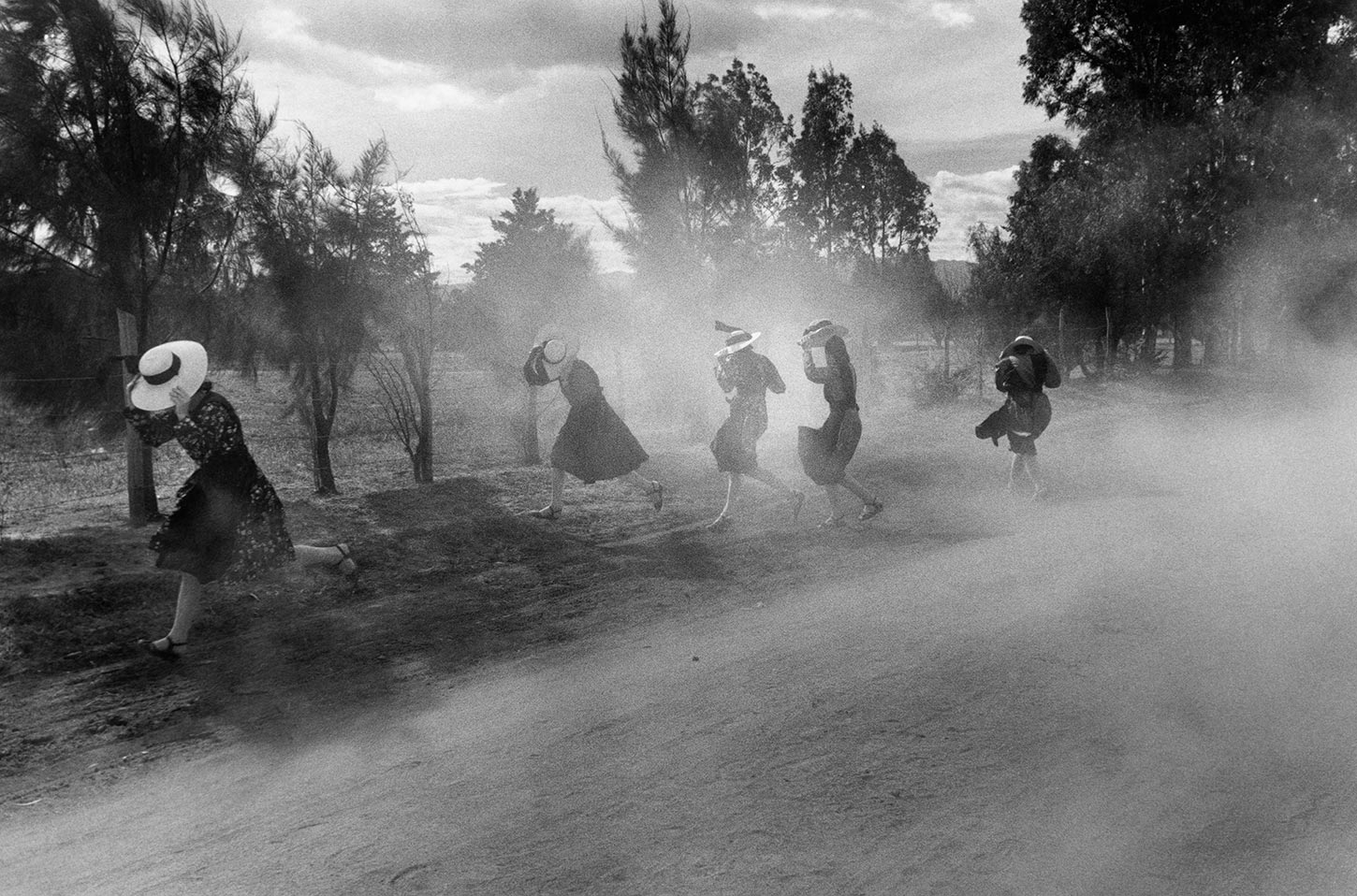 Young Mennonite women fleeing a cloud of dust. Durango, Mexico. 1994.
