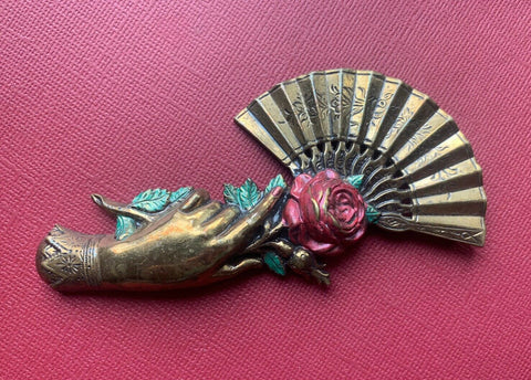 brass hand with open fan and enamelled rose