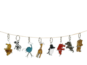 Handmade beaded animal keychains on a string for display. Eco Friendly and sustainable recycled wire with beads wrapped around them are what makes up these animals. From left to right: Golden tan lion with a whimsical brown mane, black and white zebra, aqua teal ostrich, tan giraffe, black and white penguin, red rhino, silver grey metallic elephant, and golden brown hippo. Fair Trade Decor. Fair Trade Gifts. Handmade Gifts. Handmade accessories. Handbeaded.