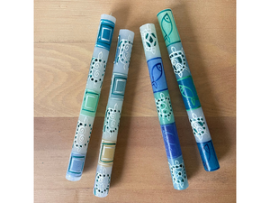 Two pairs of taper candles with white frosty base and whimsical pigment painted designs in beachy tones of sand tan, light blue, turquoise, deep blue, and teal. Turtles and fish designs with abstract squares and polkadots.