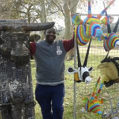 The artist, Godfrey at a craft fair in South Africa. He's standing in between various wired animal heads he created. From left to right: silver wire water buffalo head, silver wired Greater Kudu (horned antelope), other wire animal heads on the right side are colorful.